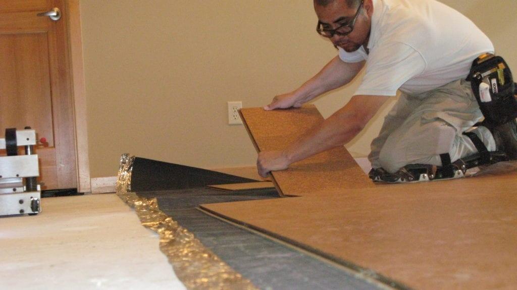 Alberto Aguilar, laying cork flooring.